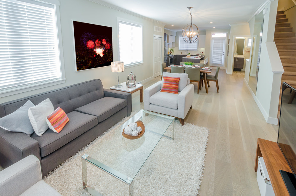 The Contemporary Modern Family Room's bright whiteness is only interrupted by a scatter of orange throw pillows